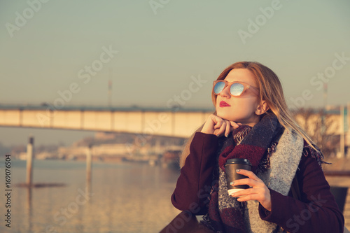 Cute attractive girl drinking coffee and enjoying the view.