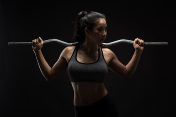 Asian sporty woman with Arms Pain,on a black background,sport,fitness, bodybuilding,healthy and lifestyle concept. © Ratthaphon Bunmi