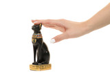 Female hand holding a cat statuette isolation