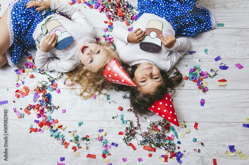 Two little girls child fashion colorful confetti on the floor and in festive hats cute and beautiful painted paper cups