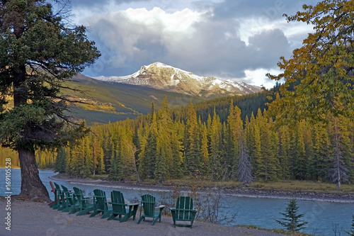 Chairs along Athabasca River with view of snow capped Mountain Peaks, Jasper National Park Alberta Canada