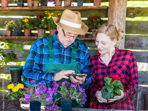 Grandfather gardener using his mobile with granddaughter