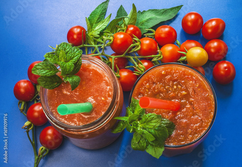 Tomato smoothie with mint. Cherry tomatoes. blue background.