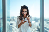Happy businesswoman using her mobile phone at office. - 169125751