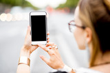 Mockup image of the woman holding a smart phone outdoors on the street background