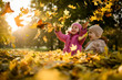 Leinwandbild Motiv Kids having fun in park, throwing up leaves.