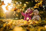 Kids having fun in park, throwing up leaves. - 169164982