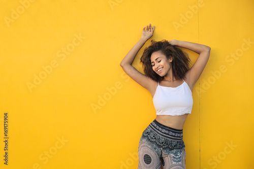 Girl dancing in front of a yellow wall