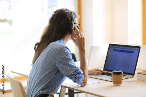 Poster Beautiful young business woman sitting at office desk and talking on cell phone. Business woman