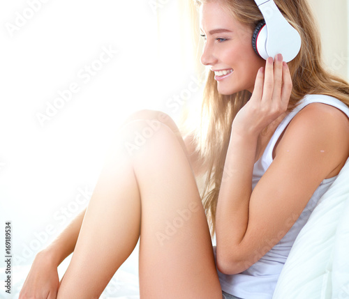 Fotobehang Muziek Portrait of beautiful woman in morning listening music sitting on bed at home