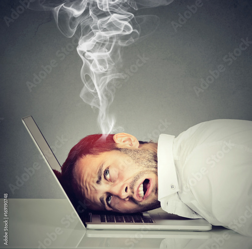 Stressed employee man with overheated brain using laptop Poster