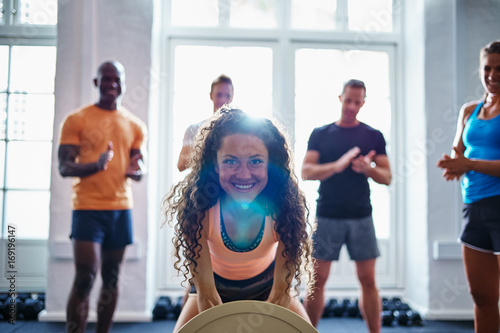 Smiling woman weightlifting with friends clapping in the backgro