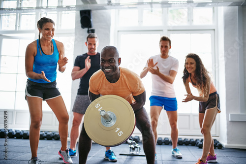 People cheering on their friend lifting weights in a gym