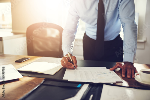 Businessman leaning on his office desk signing financial documen