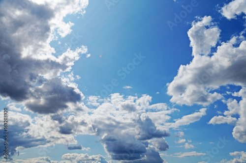 Foto Murales Fluffy white clouds on a blue sky.