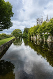 Galway, Ireland - August 3, 2017: Corrib River arm is channeled between walls in park over which Saint Vincents Convent of Mercy towers show. Cloudscape and lots of green.
