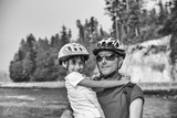 Happy father and daughter with helmet smiling during a bike trip - 169213774