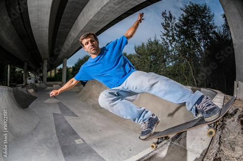 Fotobehang Skateboard Skateboarder in a concrete skatepark