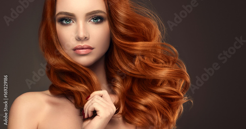 Aluminium Kapsalon Beautiful model girl with long red curly hair .Red head . Care products ,hair colouring .