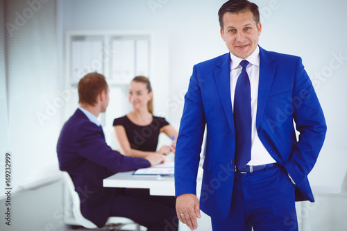 Portrait of a beautiful businesswoman standing in office with colleagues .