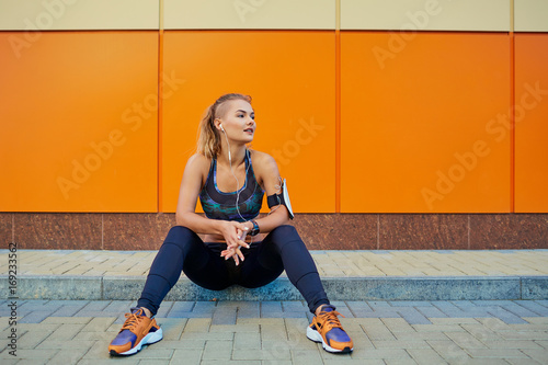 Fotobehang Muziek Girl sports listening to music with headphones sitting on orange background.