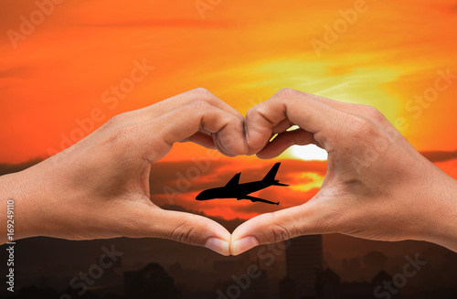 Foto op Canvas UFO hand forming a heart shape and silhouette airplane with sunset light with copy space add text