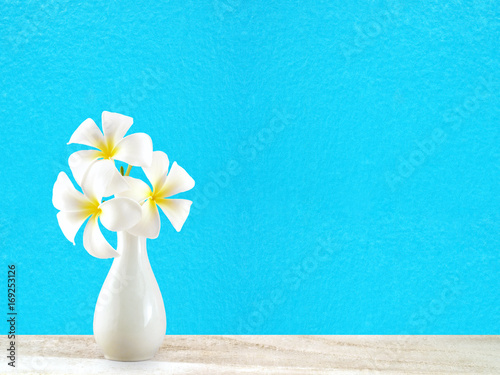 Fotobehang Plumeria white plumeria or frangipani flowers in white ceramic vase on wooden floor with blue cement wall background, tropical flowers bloom in summer for home decorating or Asian-style spa