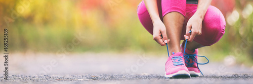 Foto Spatwand Hardlopen Running shoes runner woman tying laces for autumn run in forest park panoramic banner copy space. Jogging girl exercise motivation heatlh and fitness.