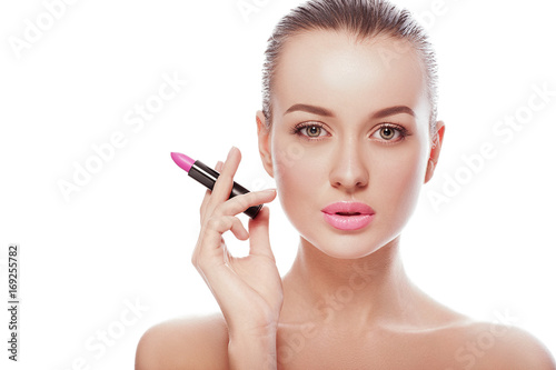 Close up beauty portrait of young woman with clean fresh perfect skin and nude makeup look at camera and holding lipstick like a cigarette. Spa, cosmetics, surgery, fashion concepts. Skin treatment. © victoriazarubina