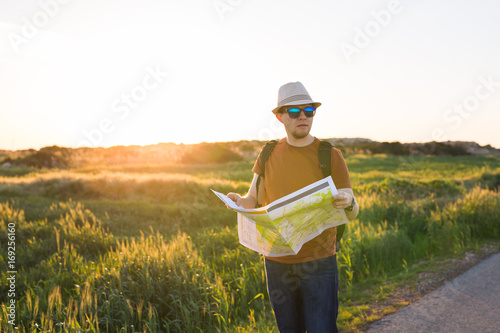 Youg man as he reads the map, traveling alone - lifestyle,people, outdoor and Holiday concept