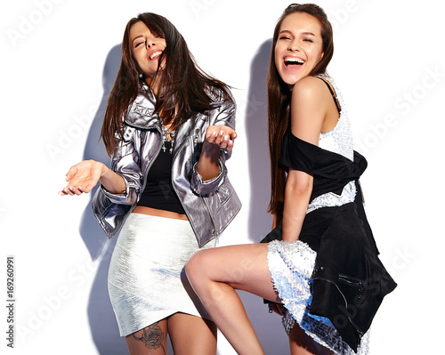 fashion portrait of two smiling brunette models in summer casual hipster clothes isolated on white