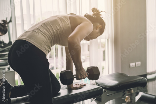 Young asian women lifting dumbbell in sport gym