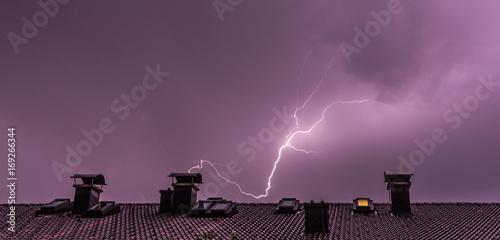 Blitzeinschlag über Häuserdach, Breitbild