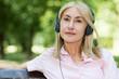 Mature smiling woman listening music