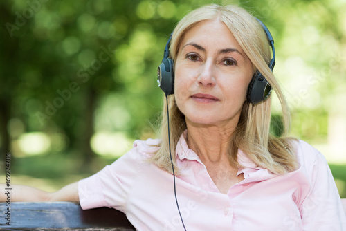 Mature smiling woman listening music