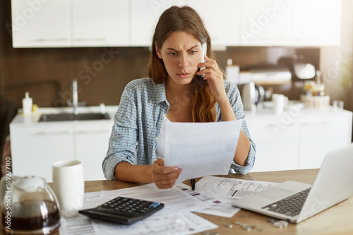 Candid shot of worried young European female dressed casually sitting at kitchen table, holding paper sheet and talking to house and utilities service representative about miscalculation in bills
