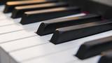 Dettaglio dei tasti di un pianoforte antico ma ristrutturato e rimesso a nuovo. La tastiera è composta da 88 tasti, di colore bianco e nero, sui quali si riflettono i colori caldi del tramonto. - 169279762
