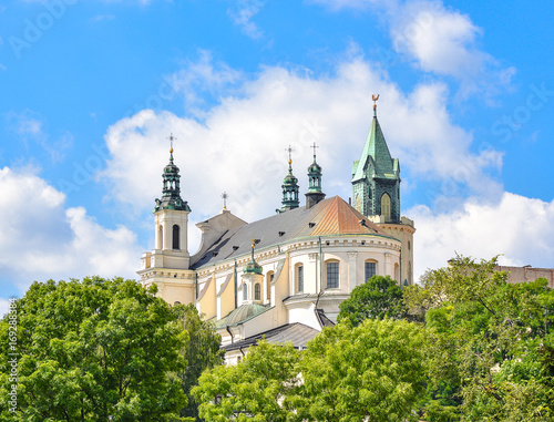 Zdjęcia na płótnie, fototapety na wymiar, obrazy na ścianę : Lublin, Poland - August 10, 2017: Beautiful view of old church green trees and bright blue sky, old city center. The Metropolitan Cathedral of St. John the Baptist and the Evangelist in Lublin, Poland