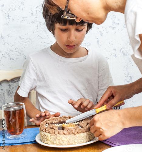 mom with son cut a birthday cake