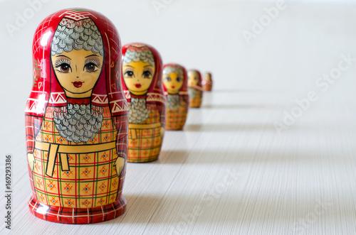 Five red matryoshka. Long shadows