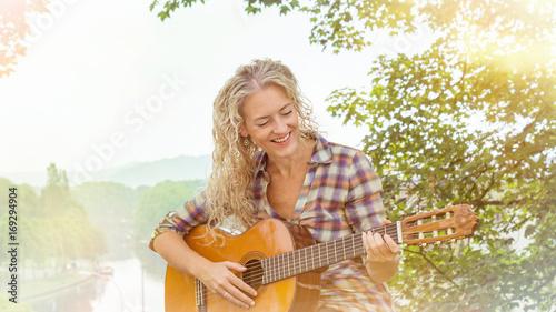 fröhlicher frau spielt gitarre.