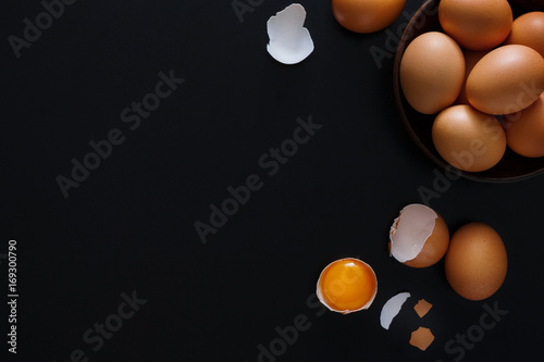 Brown and white organic eggs on wood background