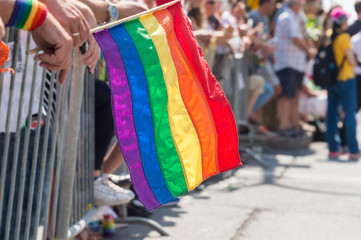 Gay rainbow flag at Montreal Gay Pride Parade 2017 with blurred spectators in the background