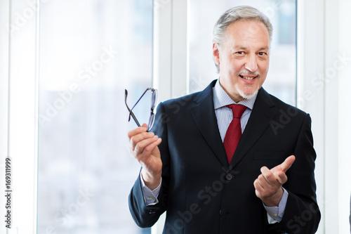 Senior manager smiling holding glasses