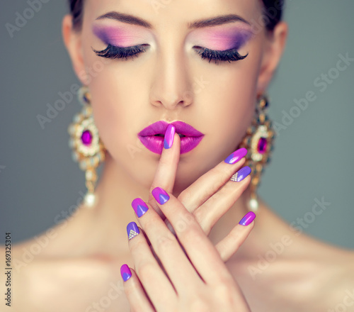 Fotobehang Manicure Beautiful girl model with fashion violet make-up and purple design manicure on nails . Jewelry and cosmetics , large violet earrings