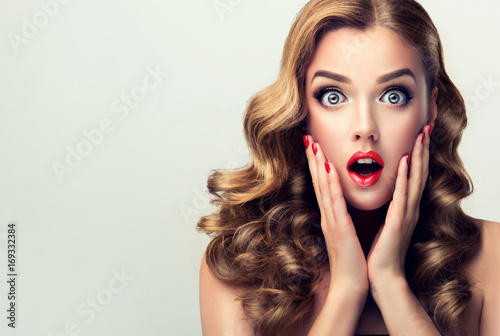 Woman with ren lips and nails surprise holds cheeks by hand .Beautiful girl  with curly hair surprised and shocked looks on you . Presenting your product. Expressive facial expressions