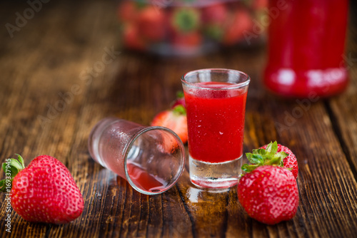 Fotobehang Sap Portion of Strawberry liqueur on wooden background, selective focus