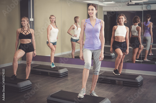 Smiling athletic women performing step aerobics Poster