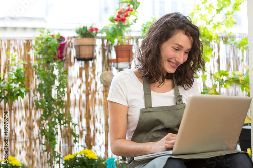 Young woman using her laptop on her city garden balcony - Technology and nature theme