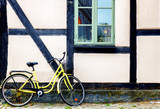 Yellow bicycle near the building facade with a window, Scandinavian style